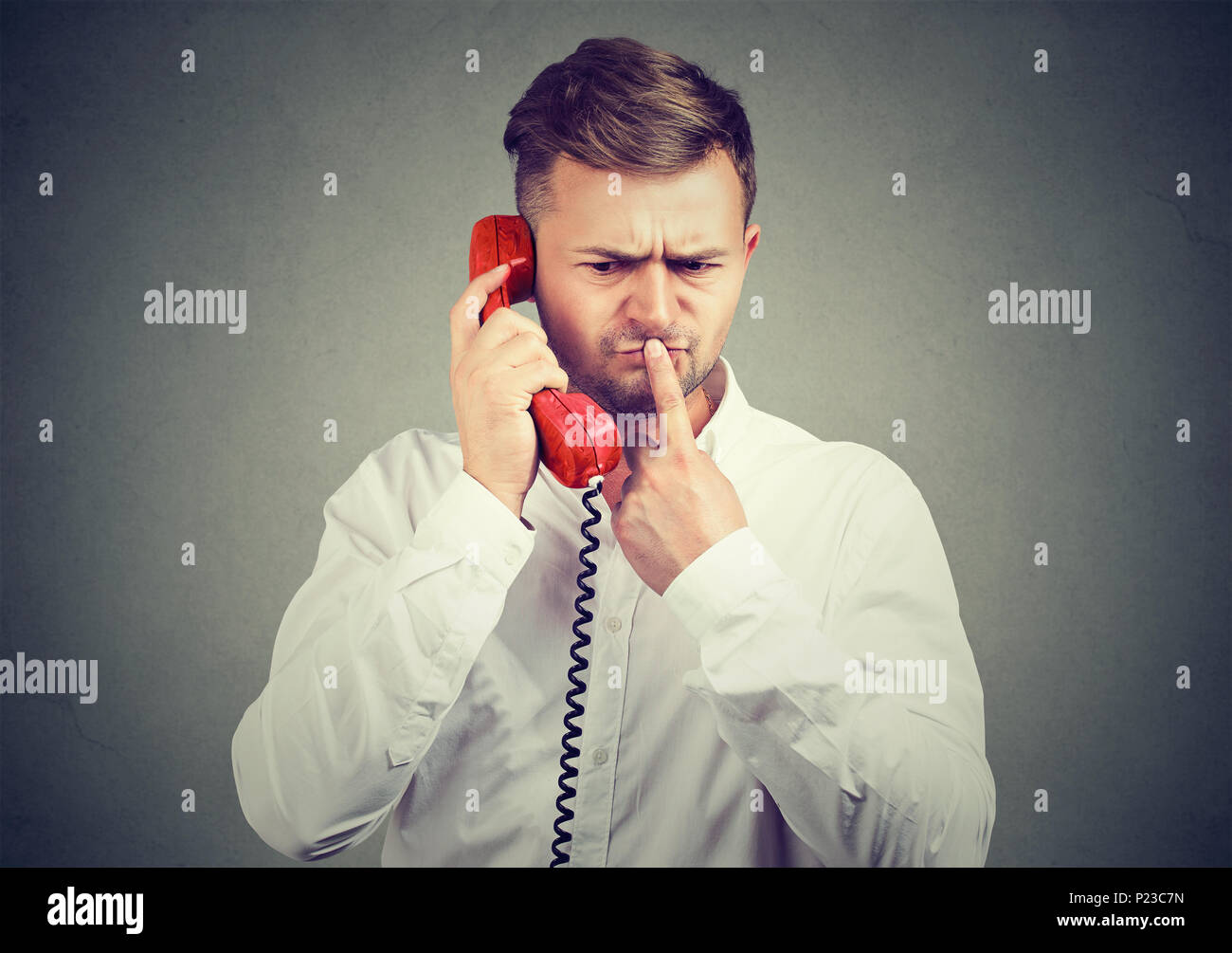 Pensive man in white shirt speaking on phone and touching lips in doubts having confusing news. - Stock Image