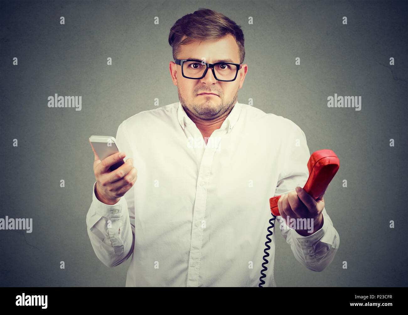 Young man holding old-fashioned red phone and modern smarpthone looking at camera in puzzlement. - Stock Image