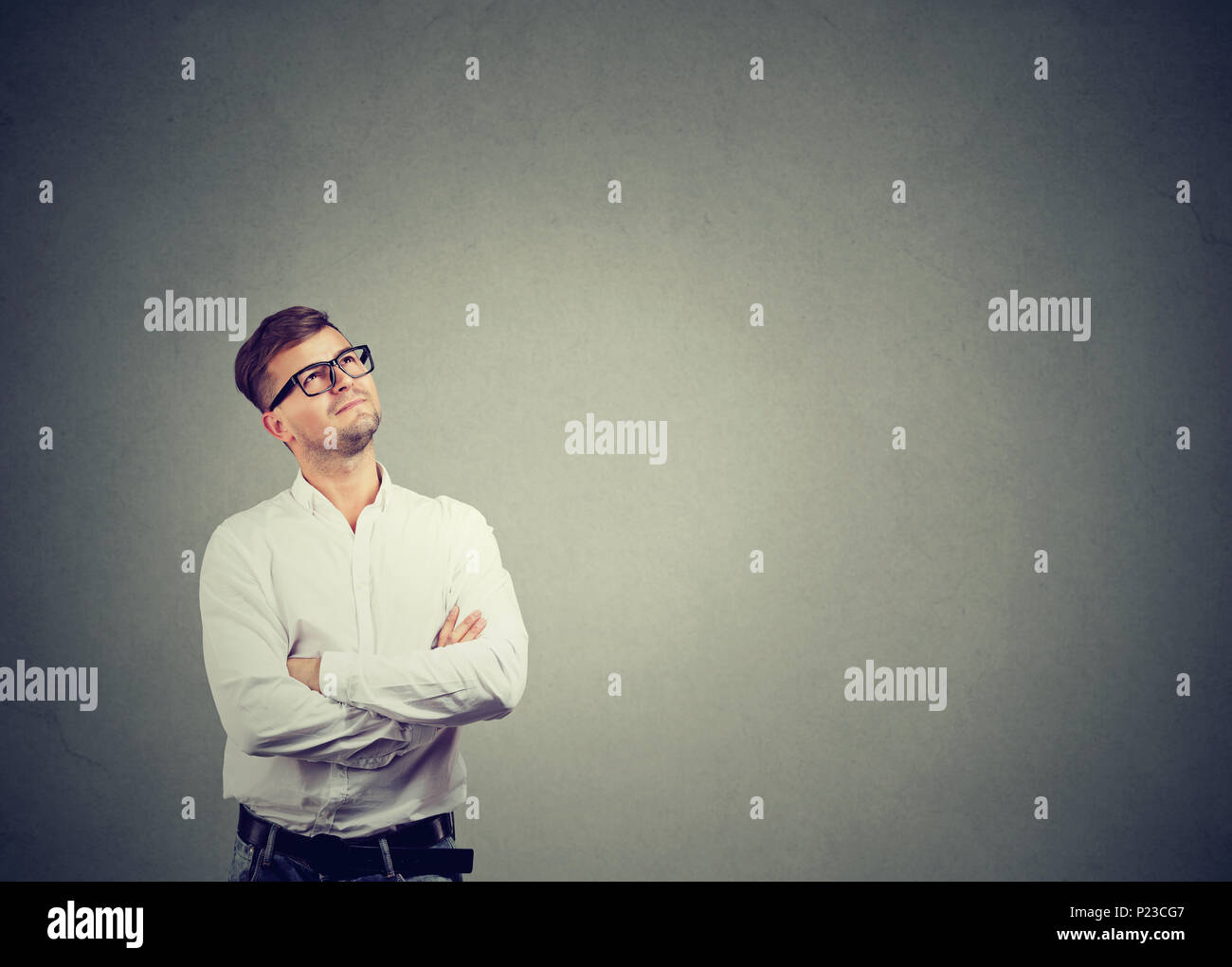 Handsome man in white shirt and glasses looking up and daydreaming dreaming of career. - Stock Image
