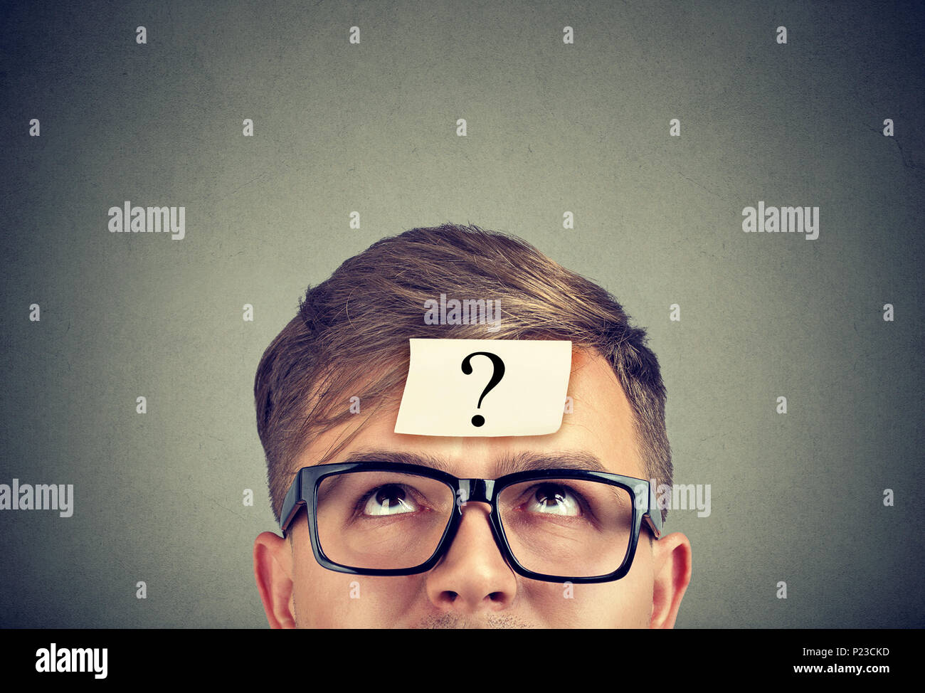 Young man wearing black glasses with question mark on forehead looking up. - Stock Image