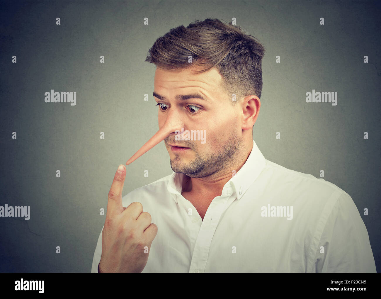 Worried shocked man with long nose. Liar concept. - Stock Image