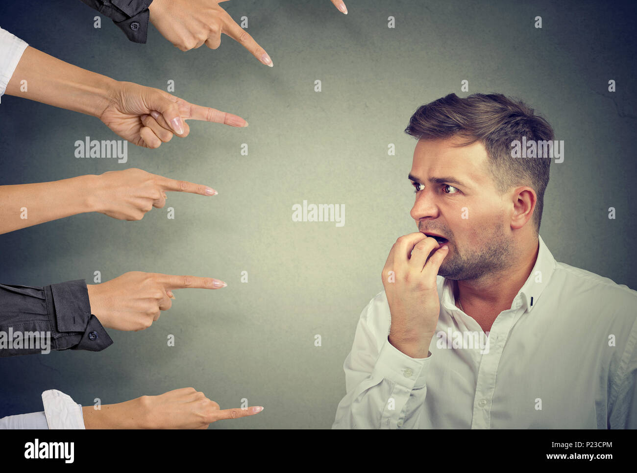 Man looking terrified while crop people pointing at him in blames. Stock Photo