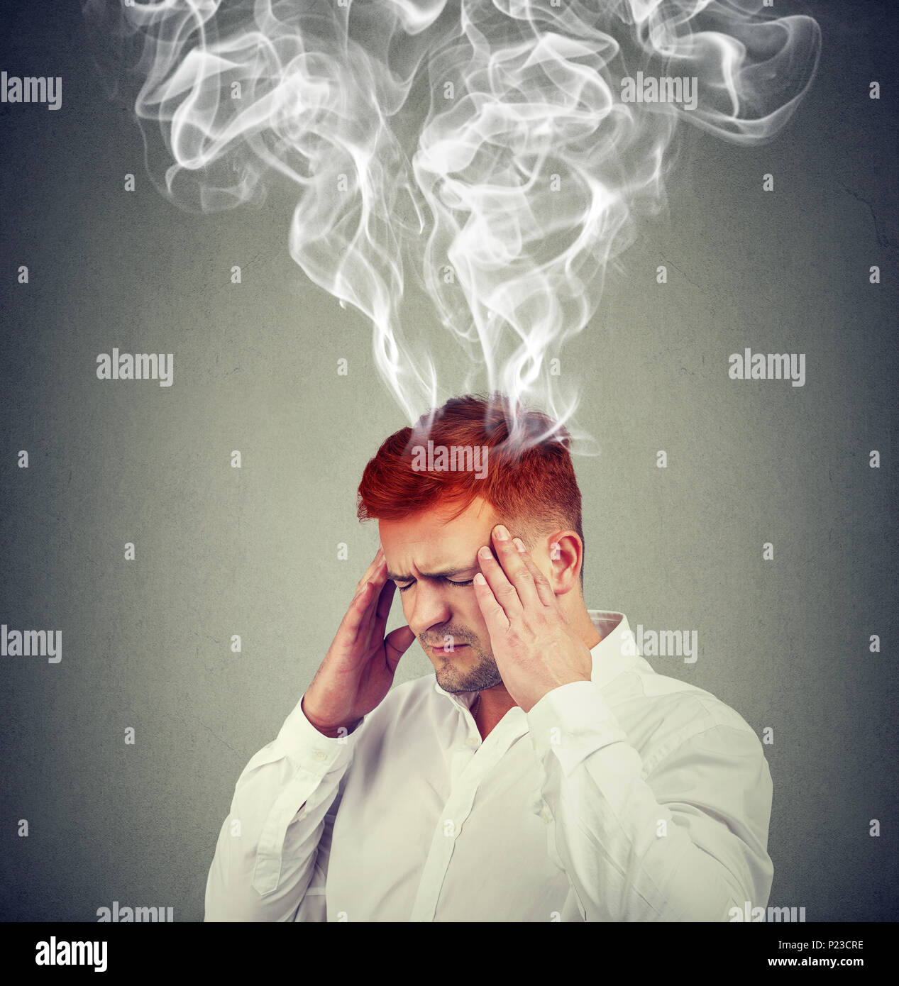 Conceptual shot of man holding hands on temples and looking frustrated with smoke coming out of head. - Stock Image