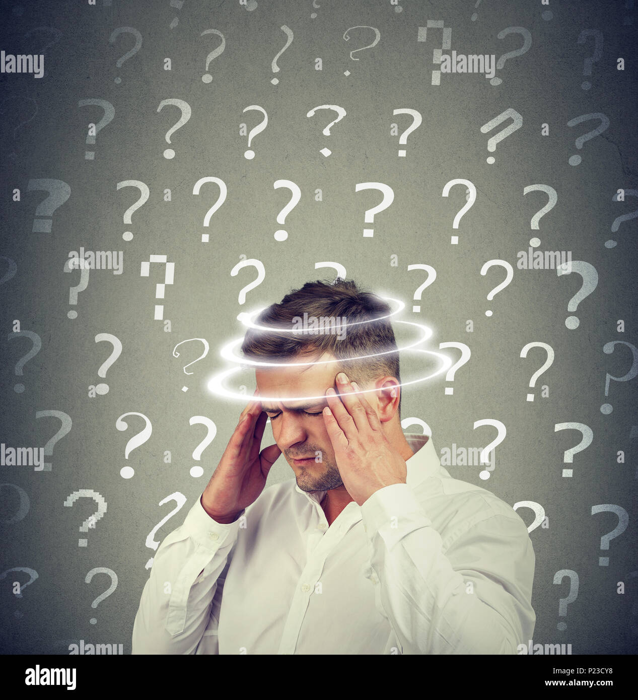 Conceptual shot of young man in shirt rubbing temples looking obsessed with plenty of questions in mind. - Stock Image