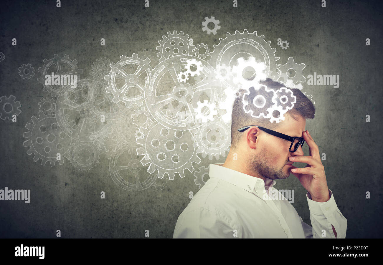Young formal man in eyeglasses brainstorming ideas about engineering looking anxious. - Stock Image