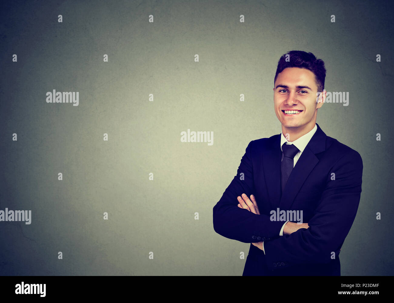 Portrait of confident cheerful businessman isolated on gray background - Stock Image