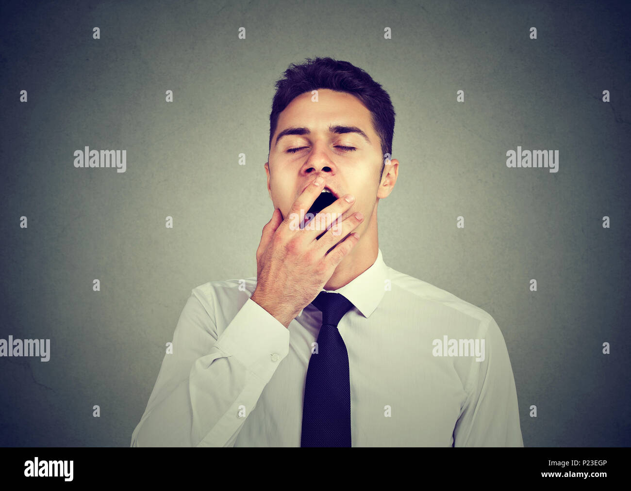 Sleepy young man yawning with hand over mouth - Stock Image