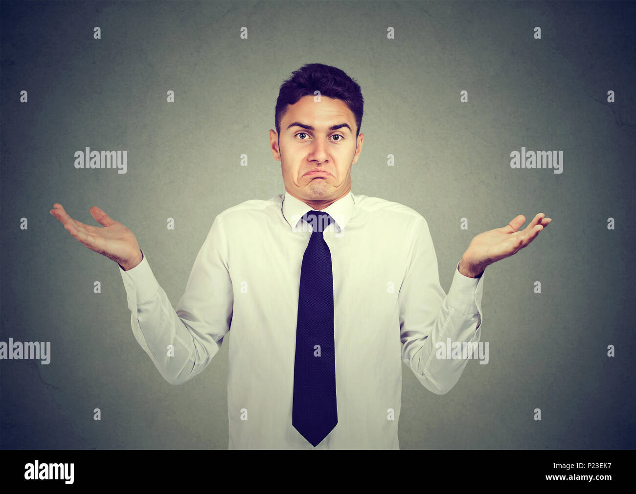 Closeup portrait young business man shrugging shoulders isolated on gray wall background. Body language - Stock Image