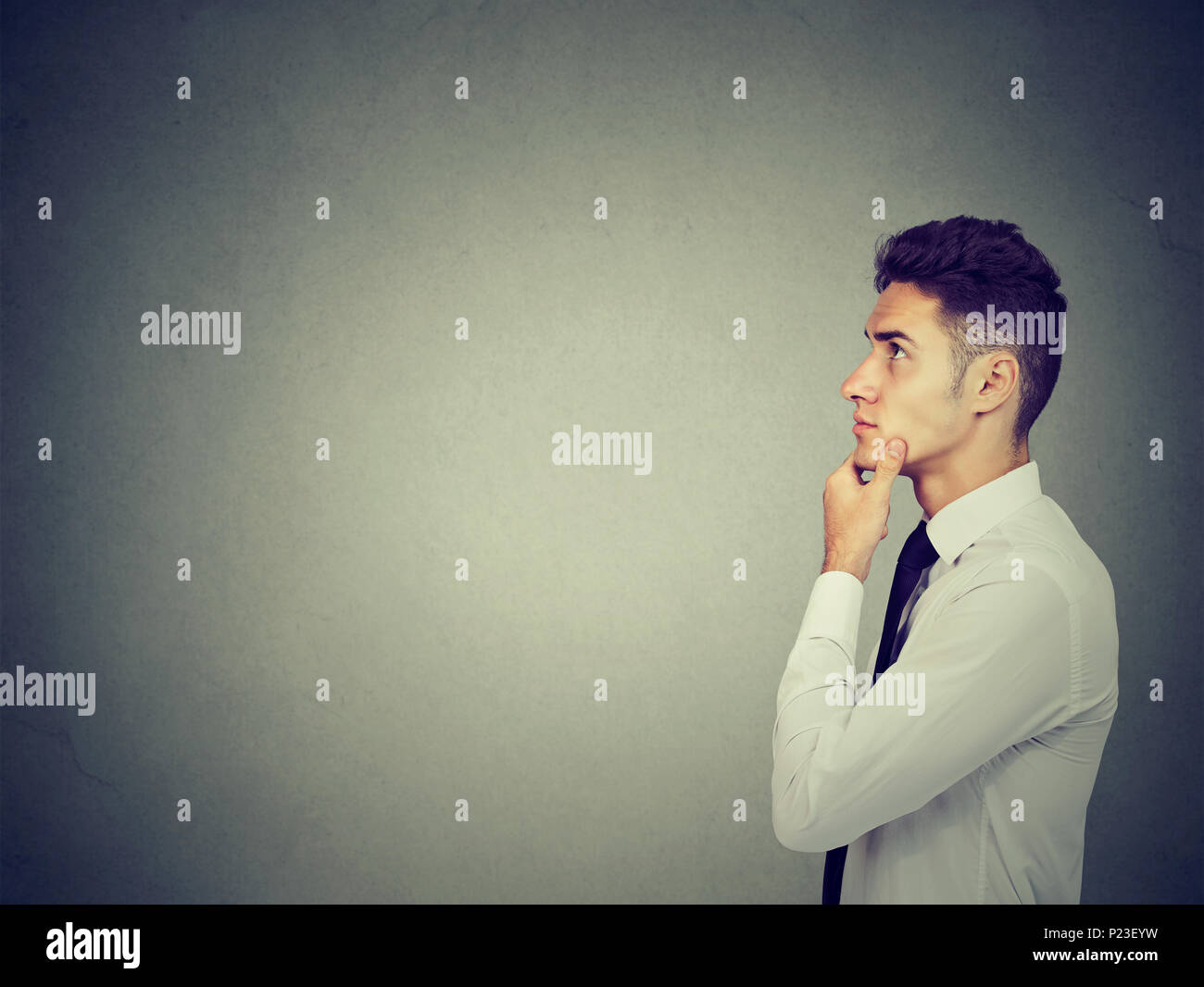 Side profile of a thinking man with hand on chin looking up - Stock Image