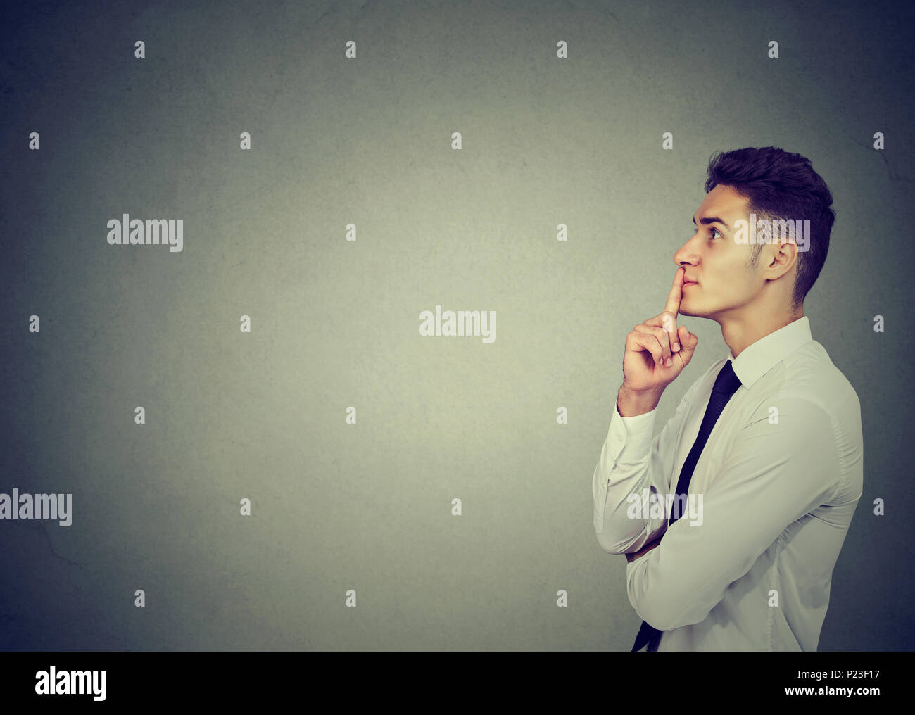 Thoughtful young business man making up his mind - Stock Image