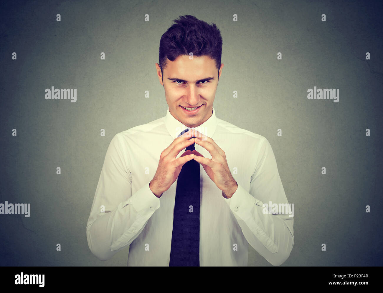 Sneaky scheming man trying to plot something isolated on gray background. Negative human emotion facial expression feeling - Stock Image