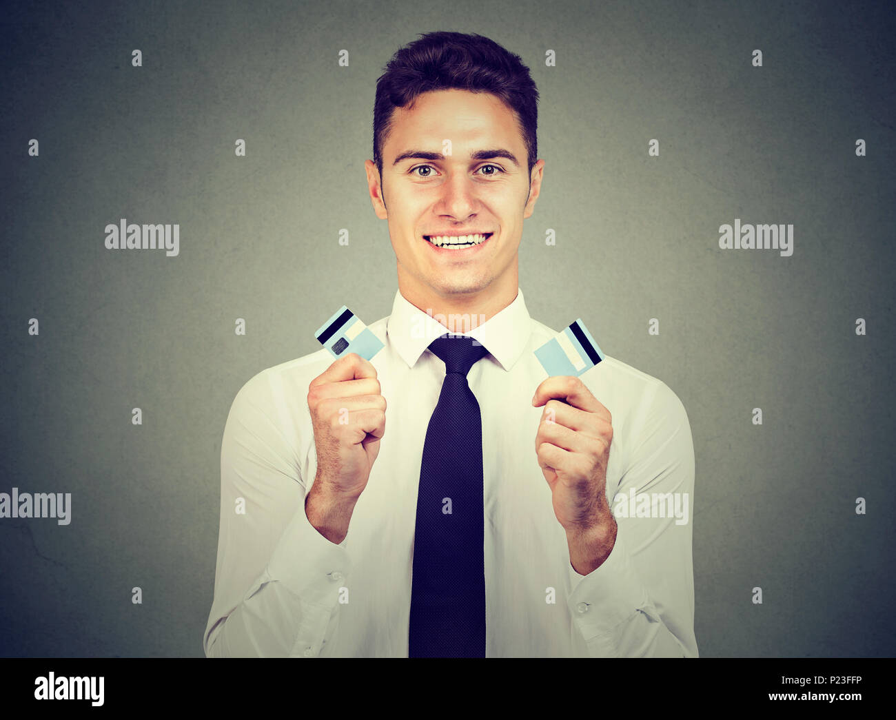 Happy debt free man holding a credit card cut in two pieces - Stock Image