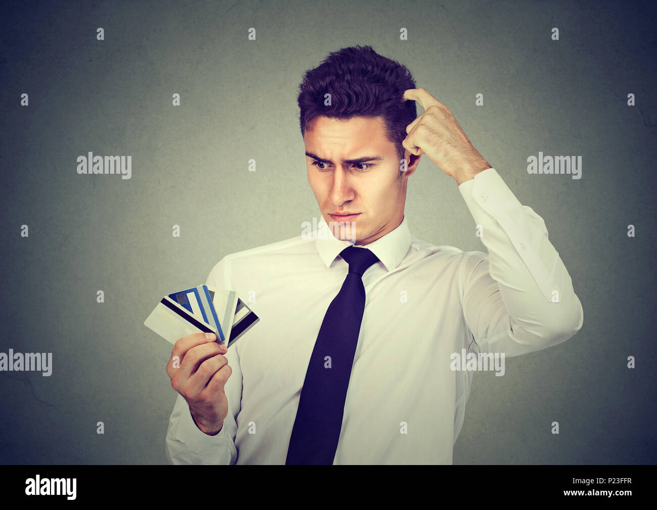 Confused man looking at many credit cards uncertain which one to choose isolated on gray background - Stock Image