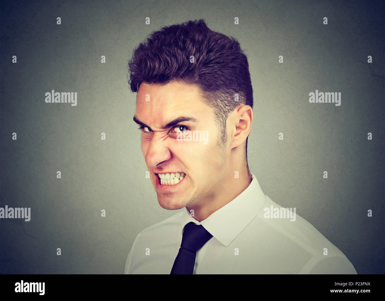 Hostile young business man looking at camera with angry face expression - Stock Image
