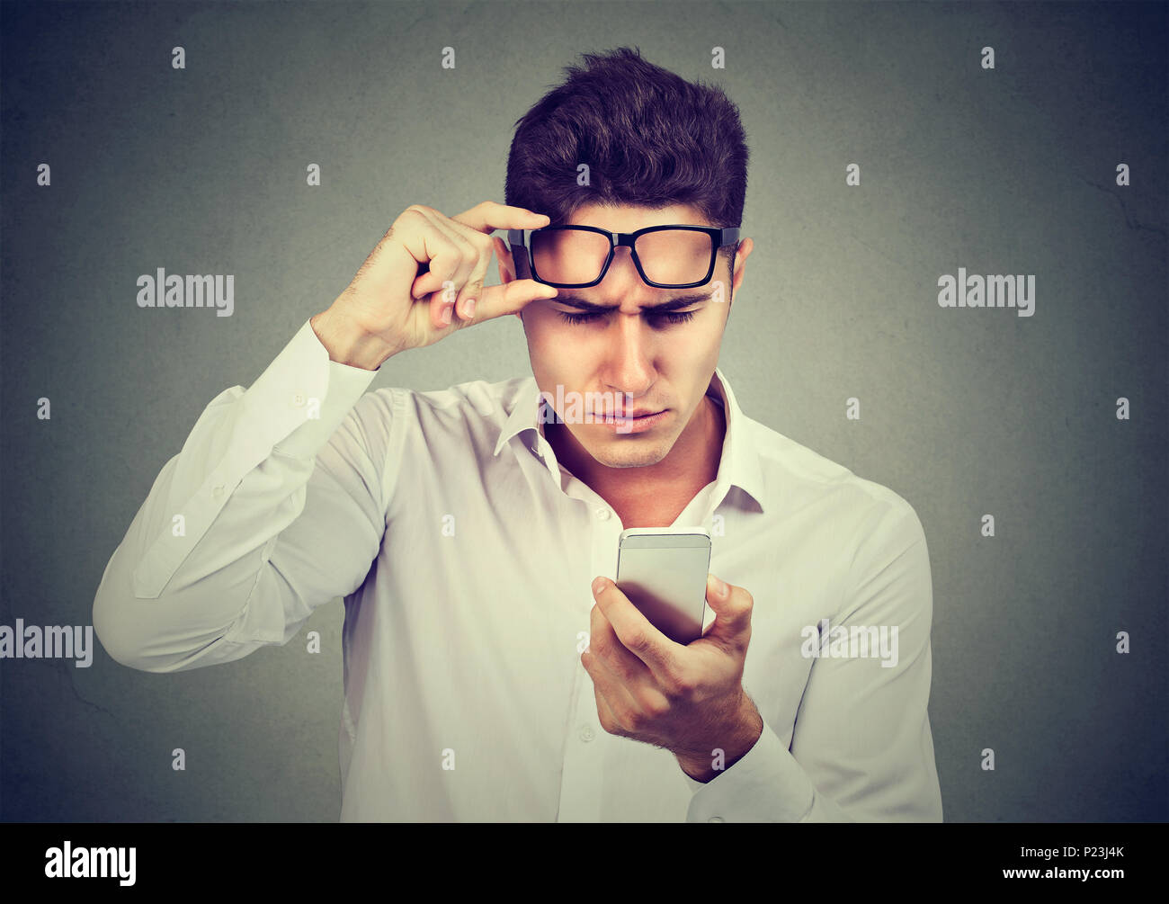 Young man with glasses having trouble seeing cell phone has vision problems. Bad text message. Human emotion perception - Stock Image