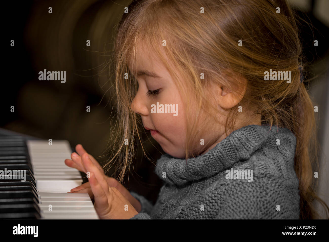 little girl playing on the keys of the piano, closeup - Stock Image