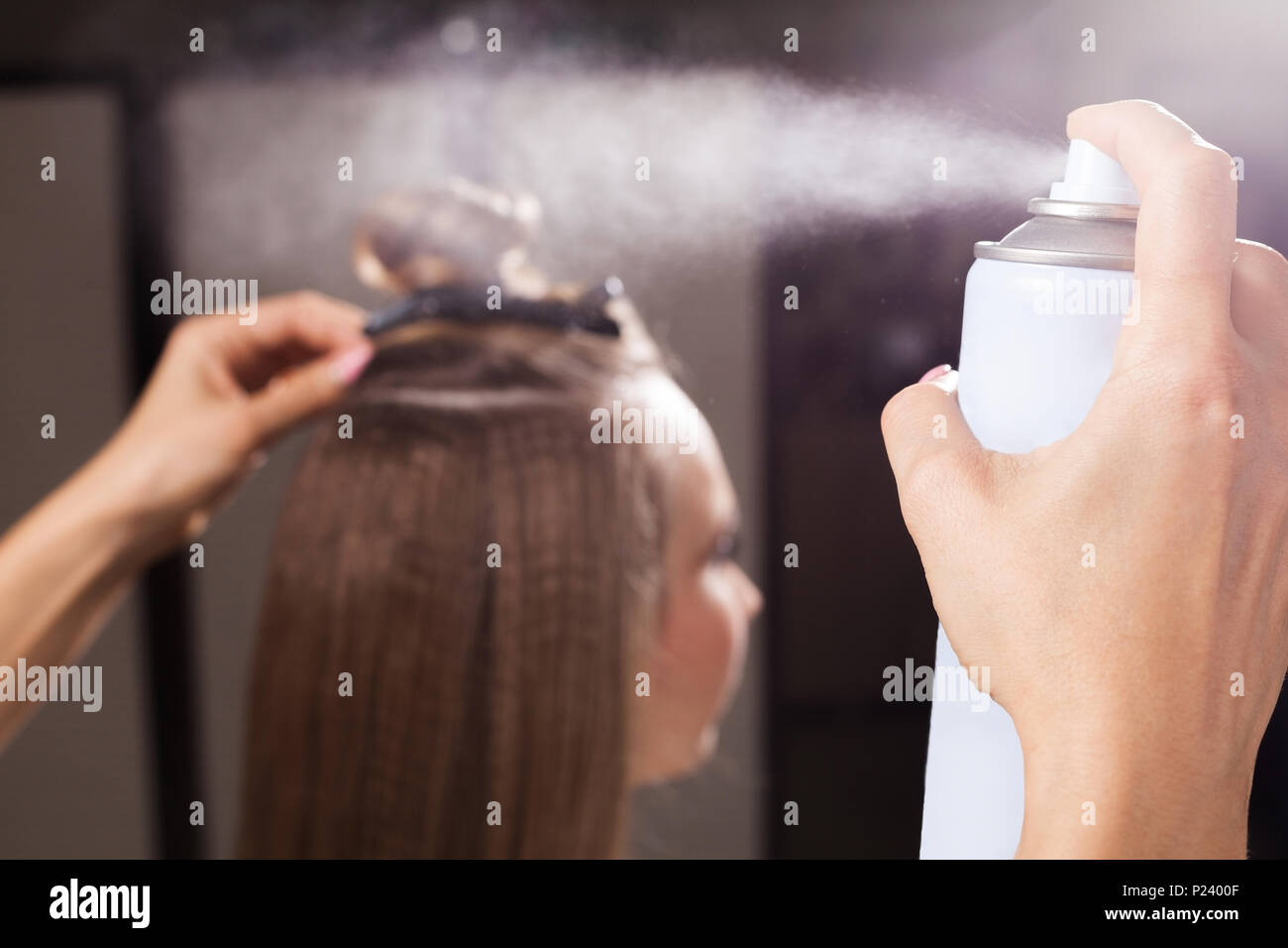 hairdresser fixing a topknot of a woman with a hair spray - Stock Image