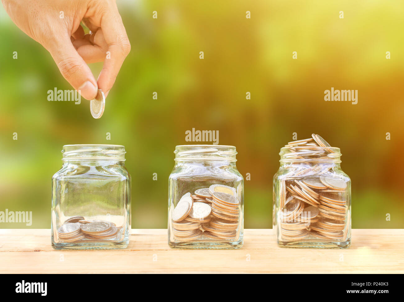 Saving and invest money concept. Conceptual hand putting coins into bottle on nature background. Business investment growth concept. Investing and int - Stock Image