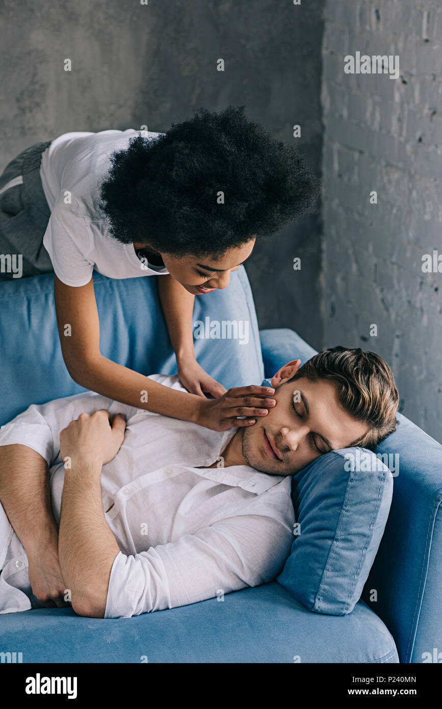 African american woman tenderly touching face of man sleeping on sofa - Stock Image