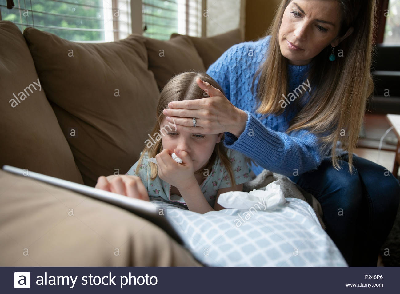 Mother checking forehead temperature of sick daughter laying on sofa - Stock Image