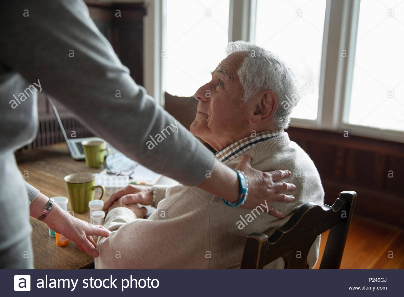Home caregiver comforting senior man at table - Stock Image