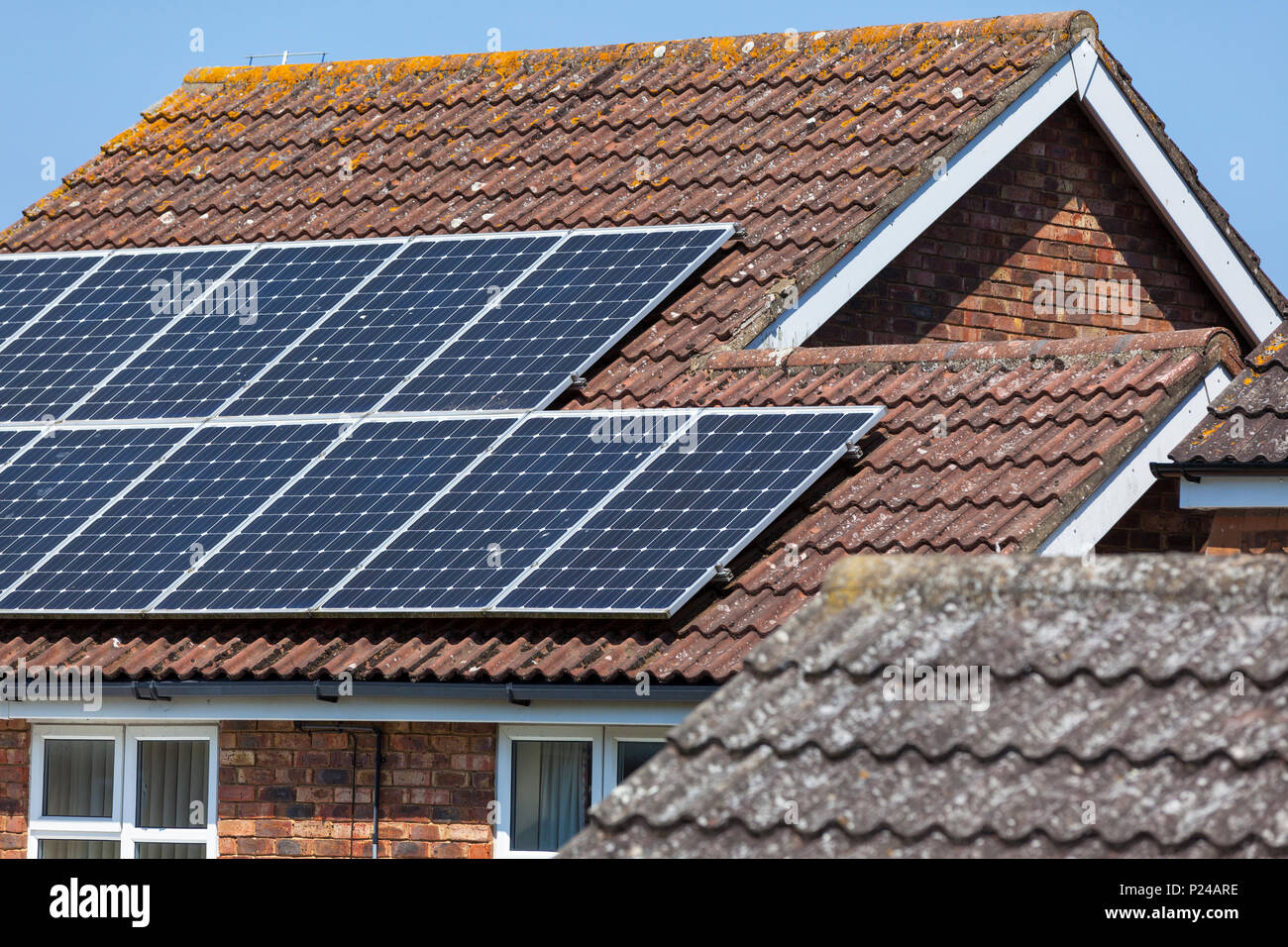 Solar panels on a detached house, uk - Stock Image