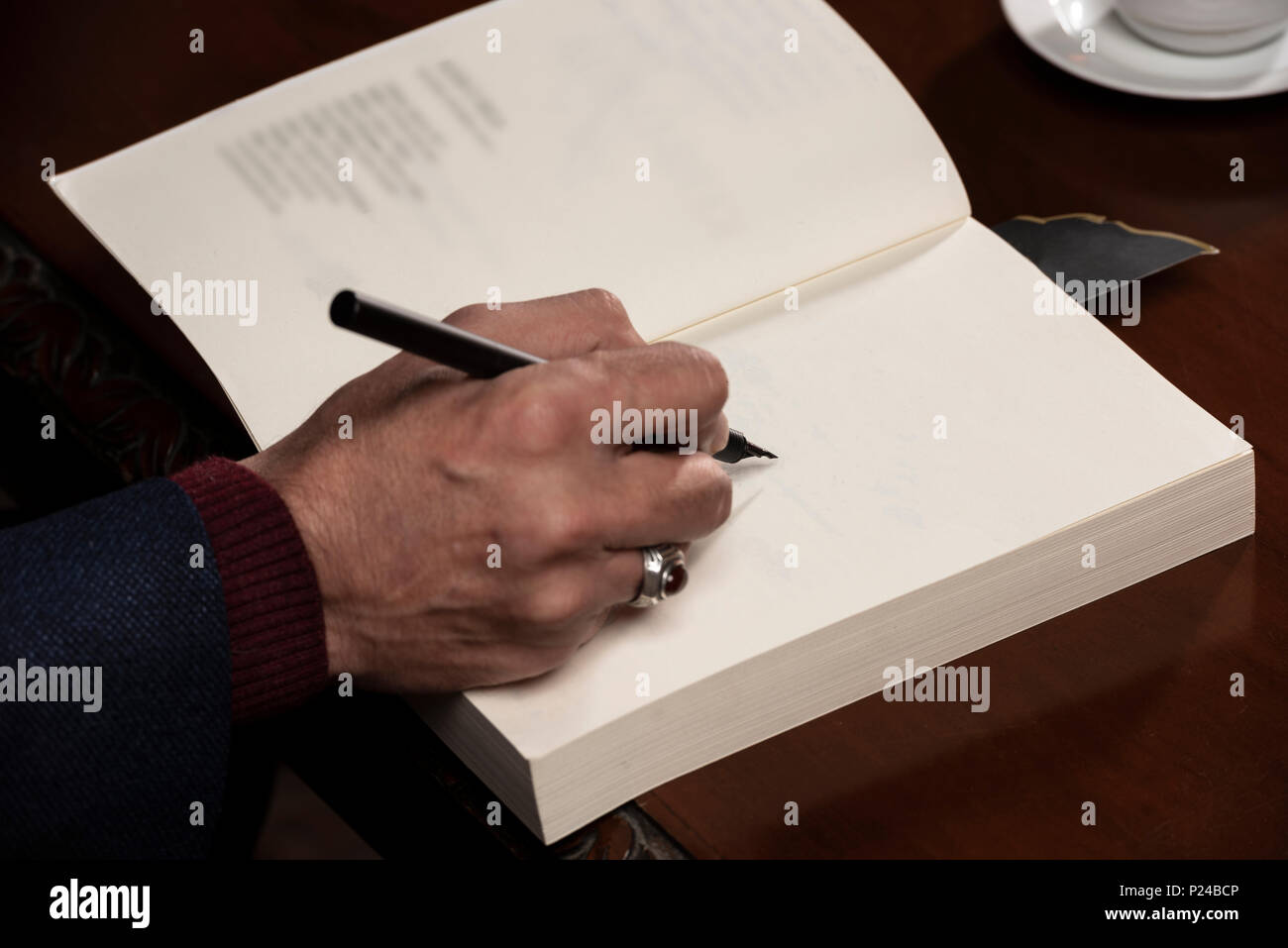 Man hand with pen writing on book. - Stock Image