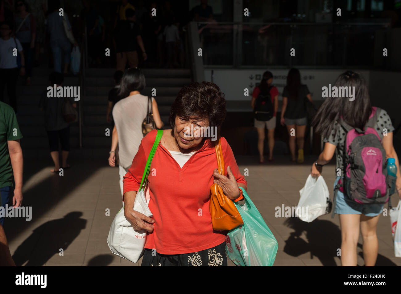 Singapore, Singapore, passersby leaving a shopping center Stock Photo