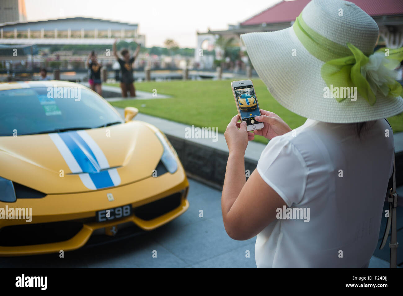 Singapore, Singapore, woman photographed a yellow Ferrari - Stock Image