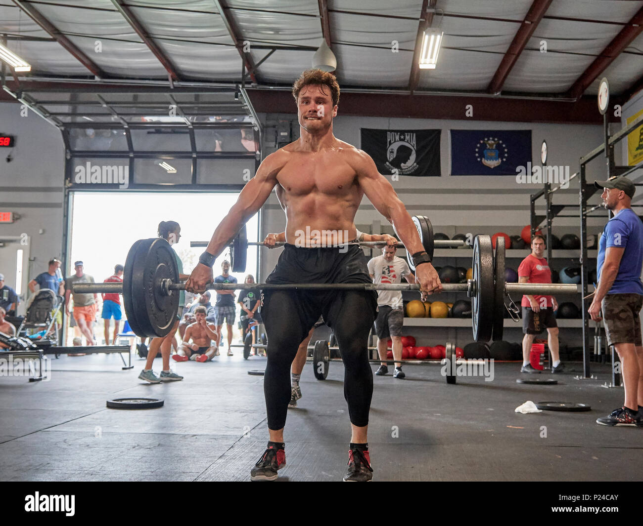 Male or man competing in a CrossFit fitness challenge competition by dead lifting weights inside a gym in Montgomery Alabama, USA. - Stock Image