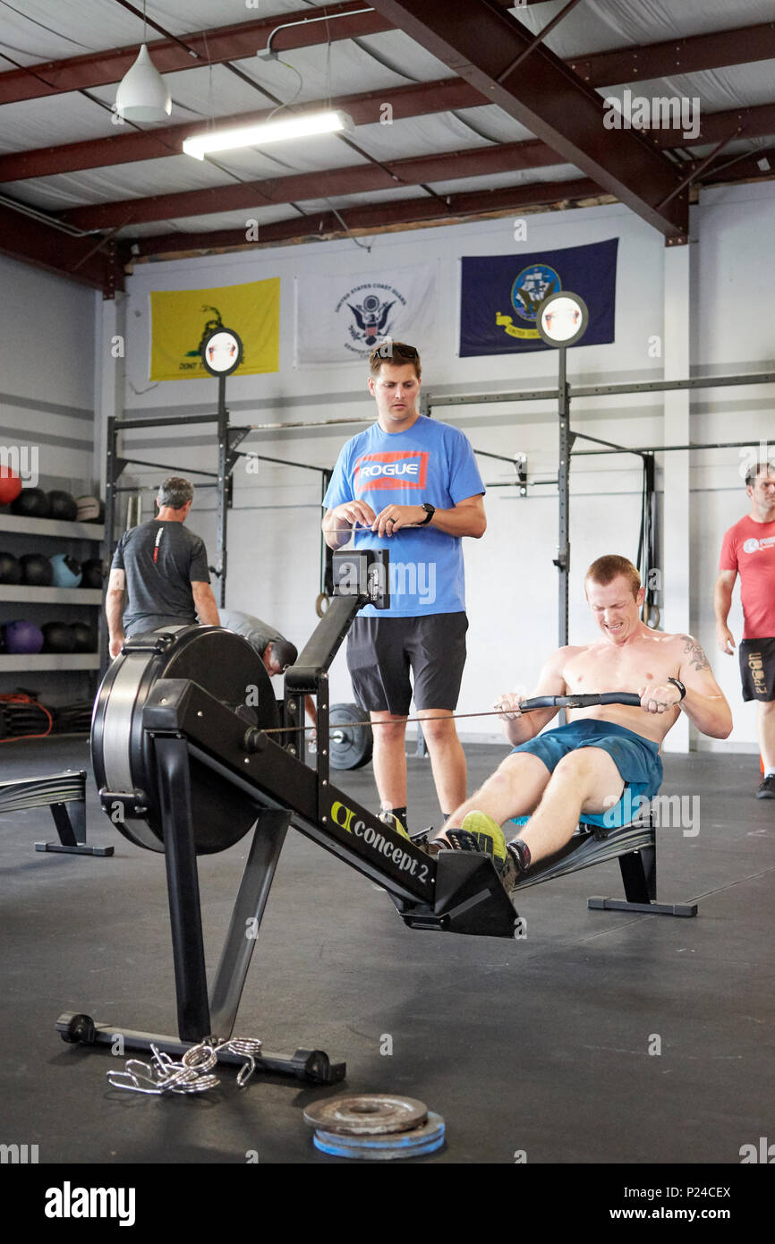 Male or man competing in a CrossFit fitness challenge competition by using a rowing machine to exhaustion inside a gym in Montgomery Alabama, USA. - Stock Image