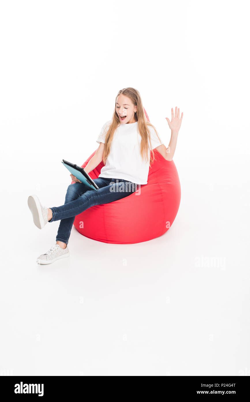 excited female youngster using digital tablet and sitting in red bean bag chair, isolated on white - Stock Image