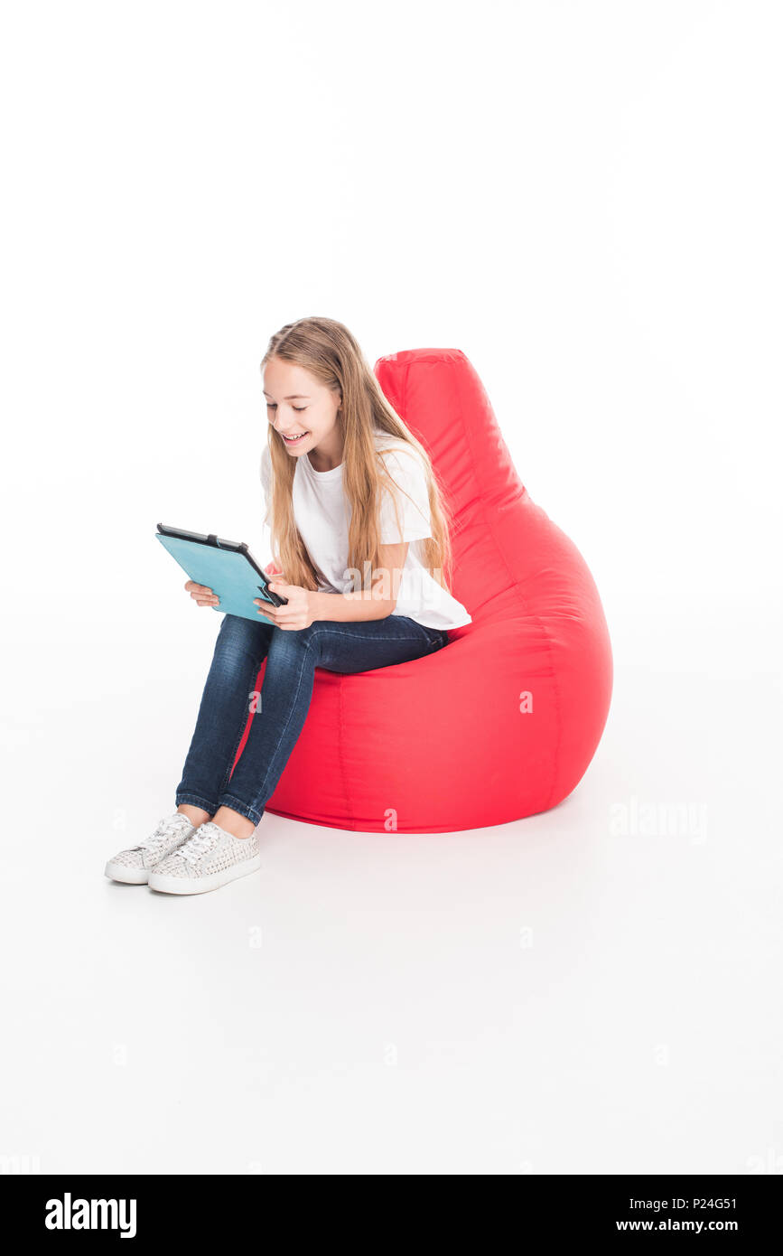 adorable female youngster using digital tablet and sitting in red bean bag chair, isolated on white - Stock Image