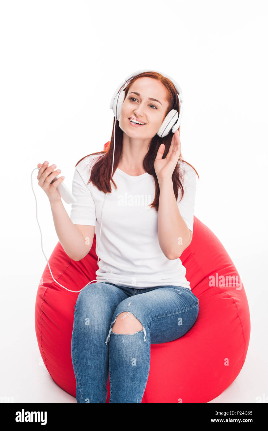 smiling young girl listening music and sitting in red bean bag chair, isolated on white - Stock Image