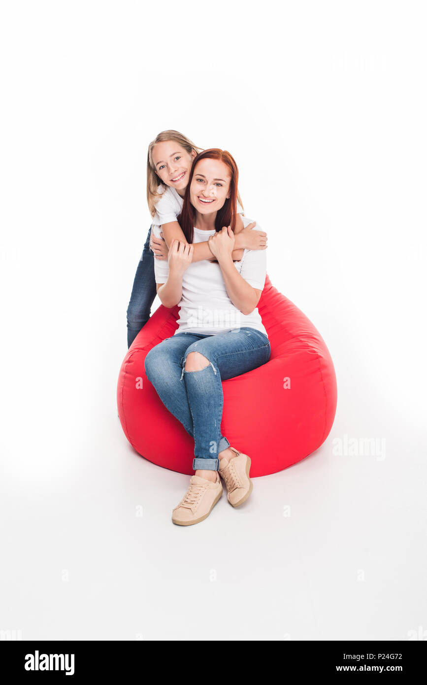 happy daughter hugging her mother while sitting in red bean bag chair, isolated on white - Stock Image