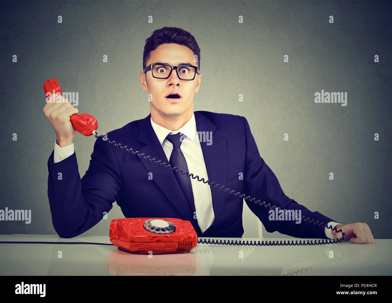 Shocked business man receiving bad news on the phone - Stock Image