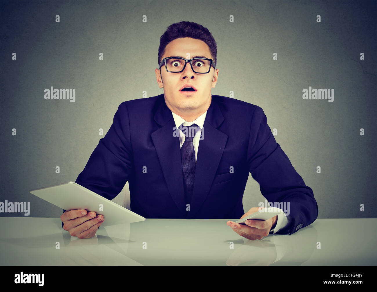Busy confused employee with smartphone and tablet computer - Stock Image