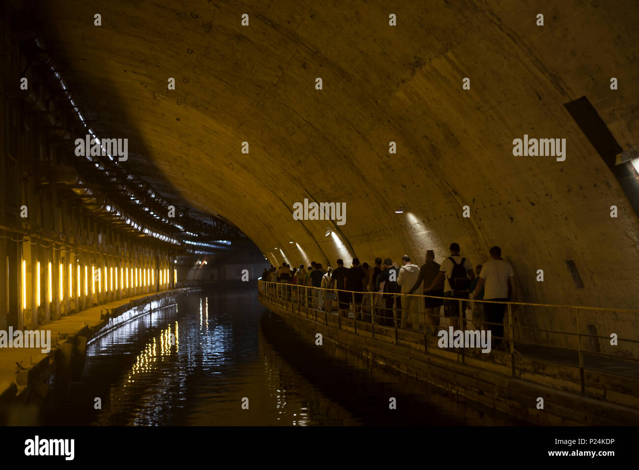 the concrete tunnel with water, the people going forward and reflection - Stock Image