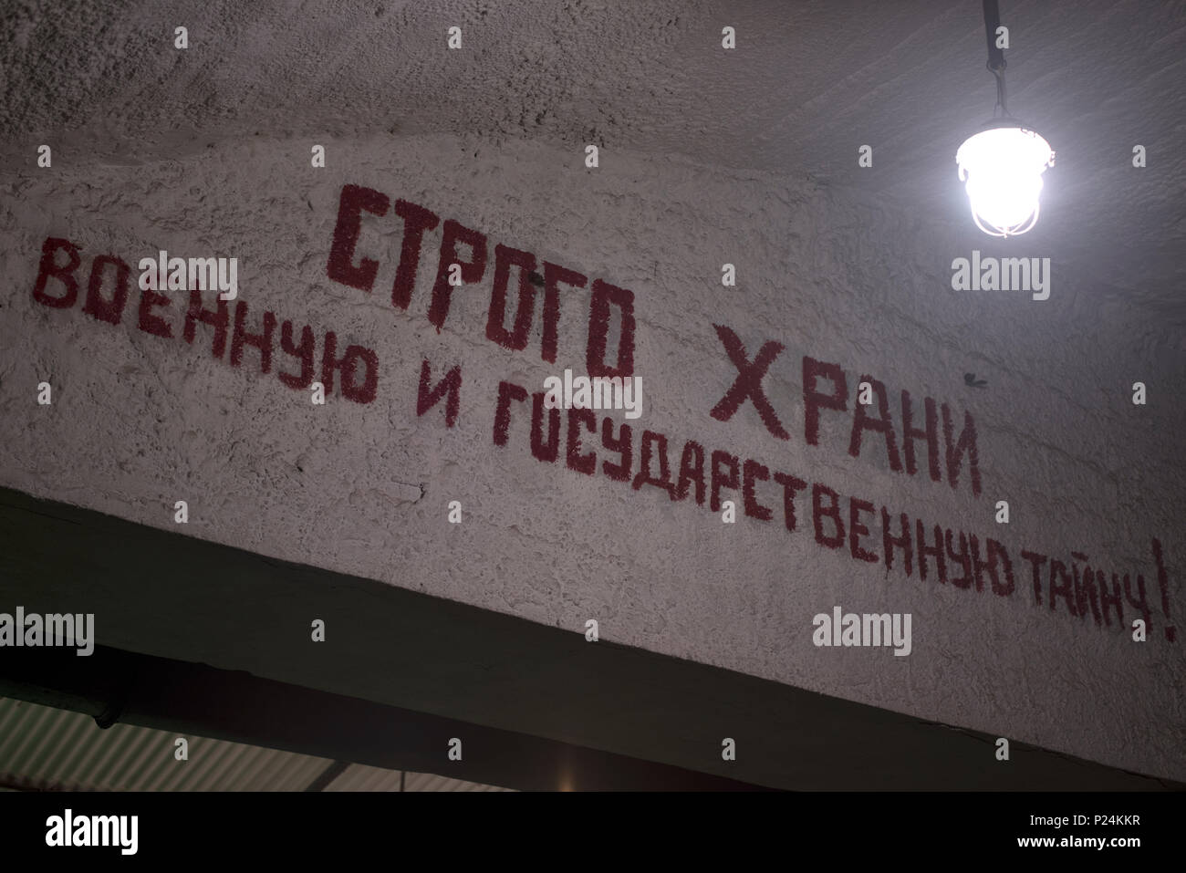 on a concrete wall paint has written a slogan, with the hanging bulb - Stock Image