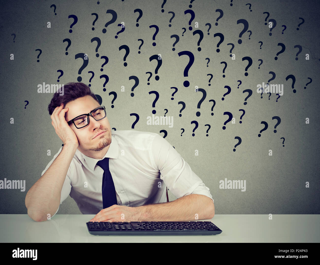 Young procrastinating office employee sitting in laziness at desk and looking away in ignorance. - Stock Image