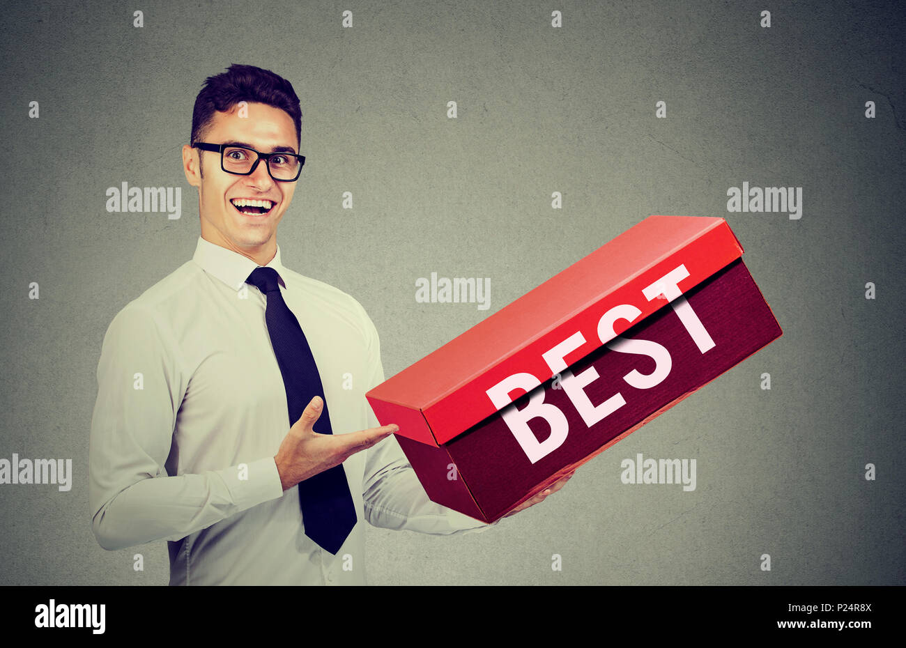 Smiling salesman business man advertising his best product in a big red box - Stock Image