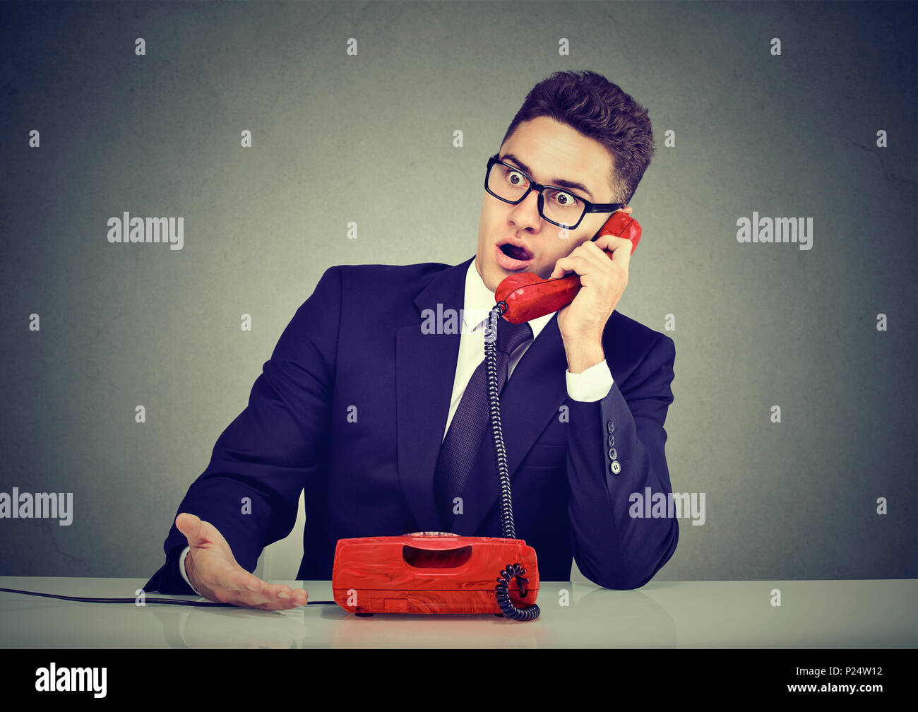 Shocked disgusted young man receiving bad news over the phone - Stock Image