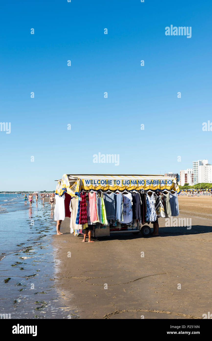 Sales stall for summer clothes with the writing 'Welcome to Lignano Sabbiadoro' on the beach of Lignano - Stock Image