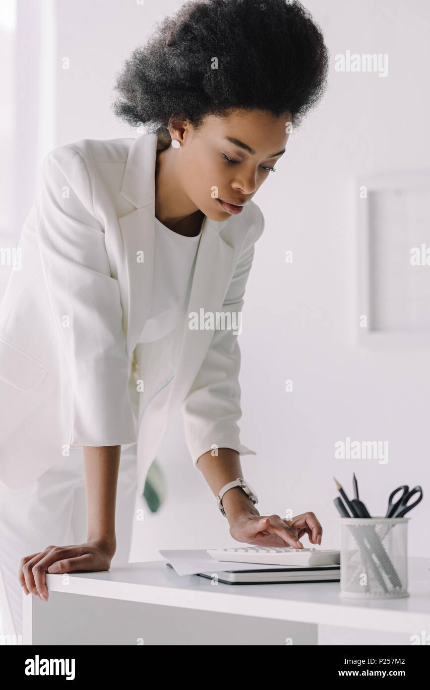attractive african american businesswoman using calculator in office Stock Photo
