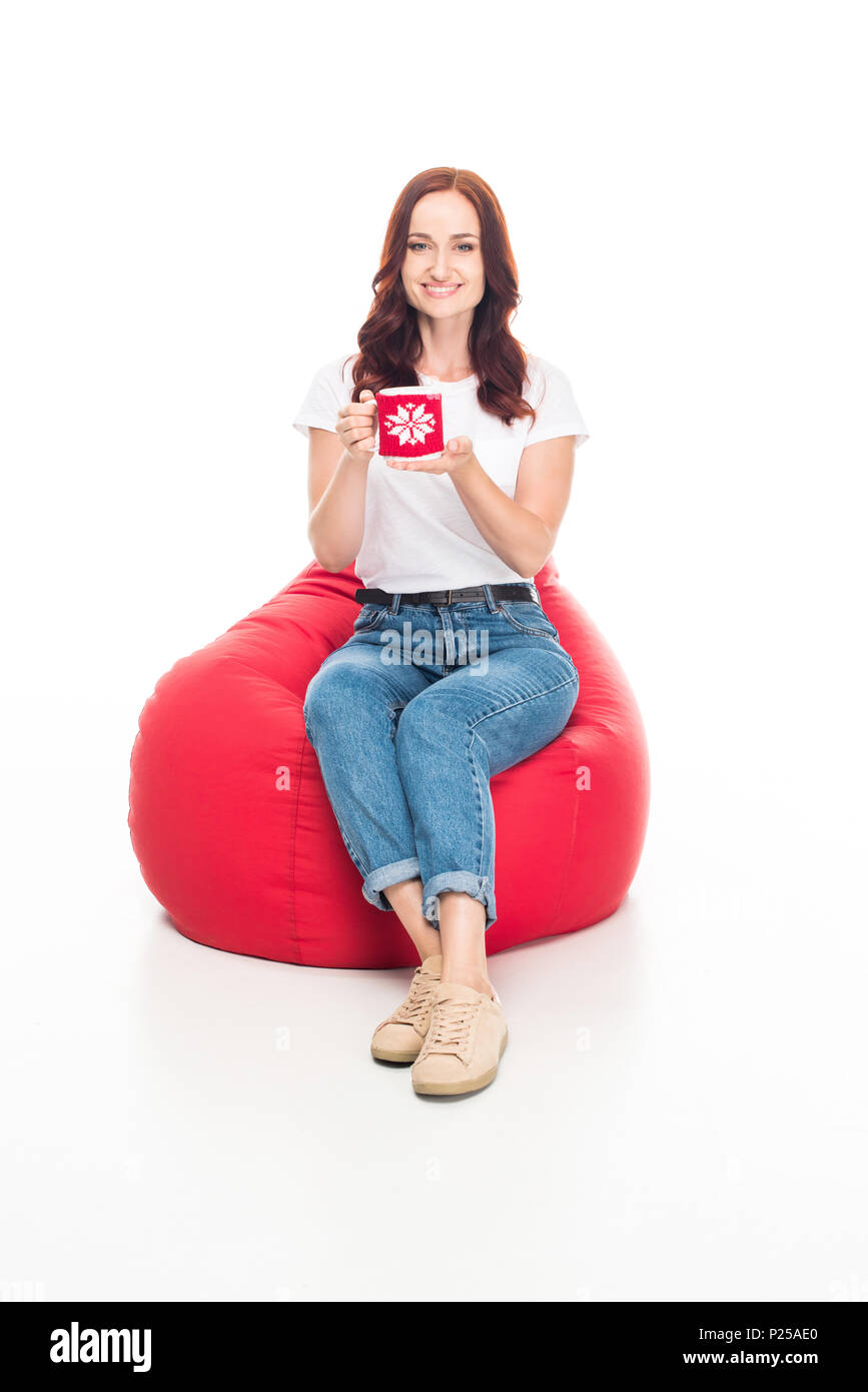 happy girl with cup of coffee sitting in red bean bag chair, isolated on white - Stock Image