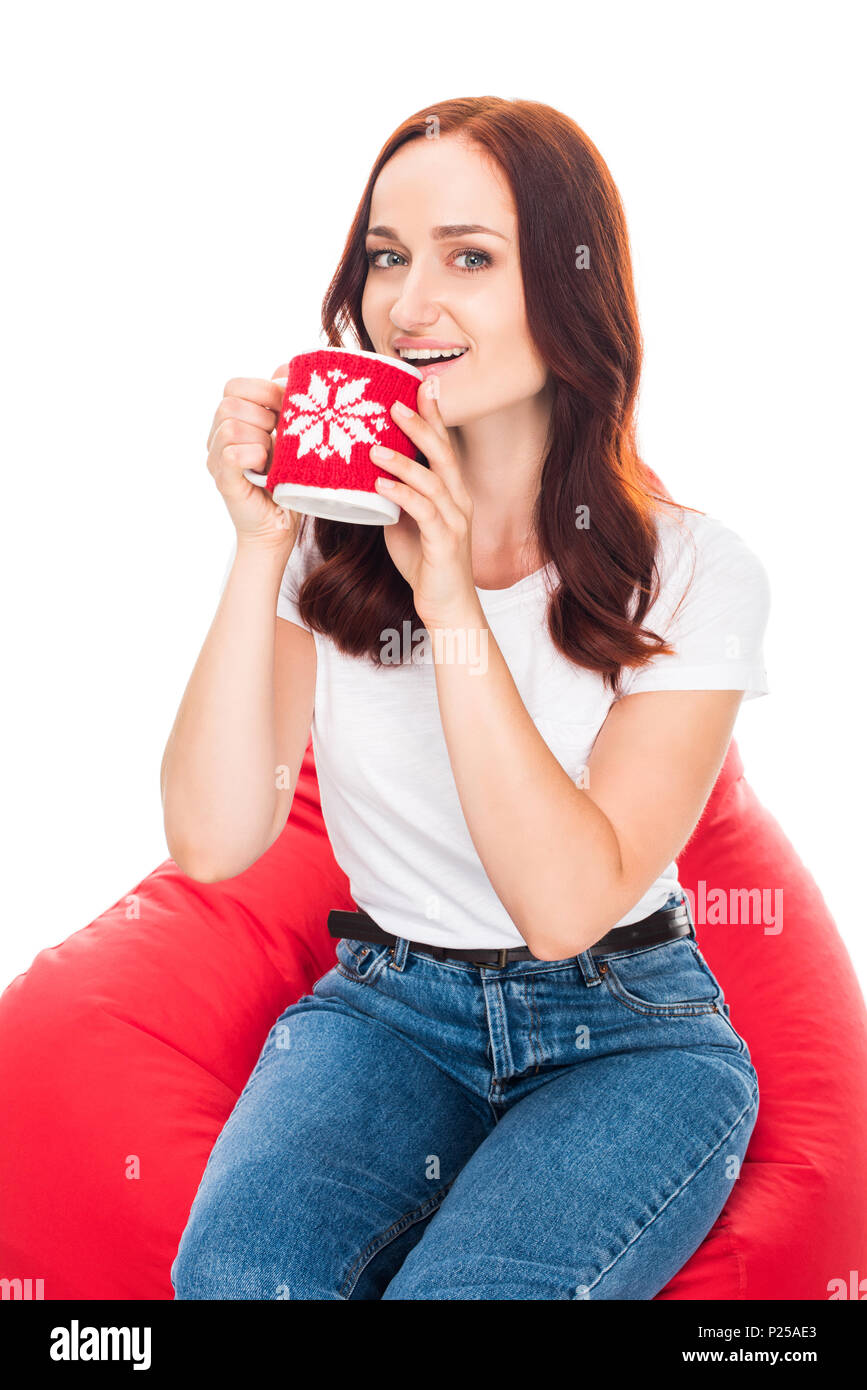 happy woman drinking coffee and sitting in red bean bag chair, isolated on white - Stock Image