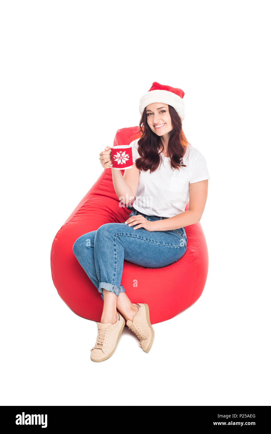 happy woman in Santa hat with cup of coffee sitting in red bean bag chair, isolated on white - Stock Image