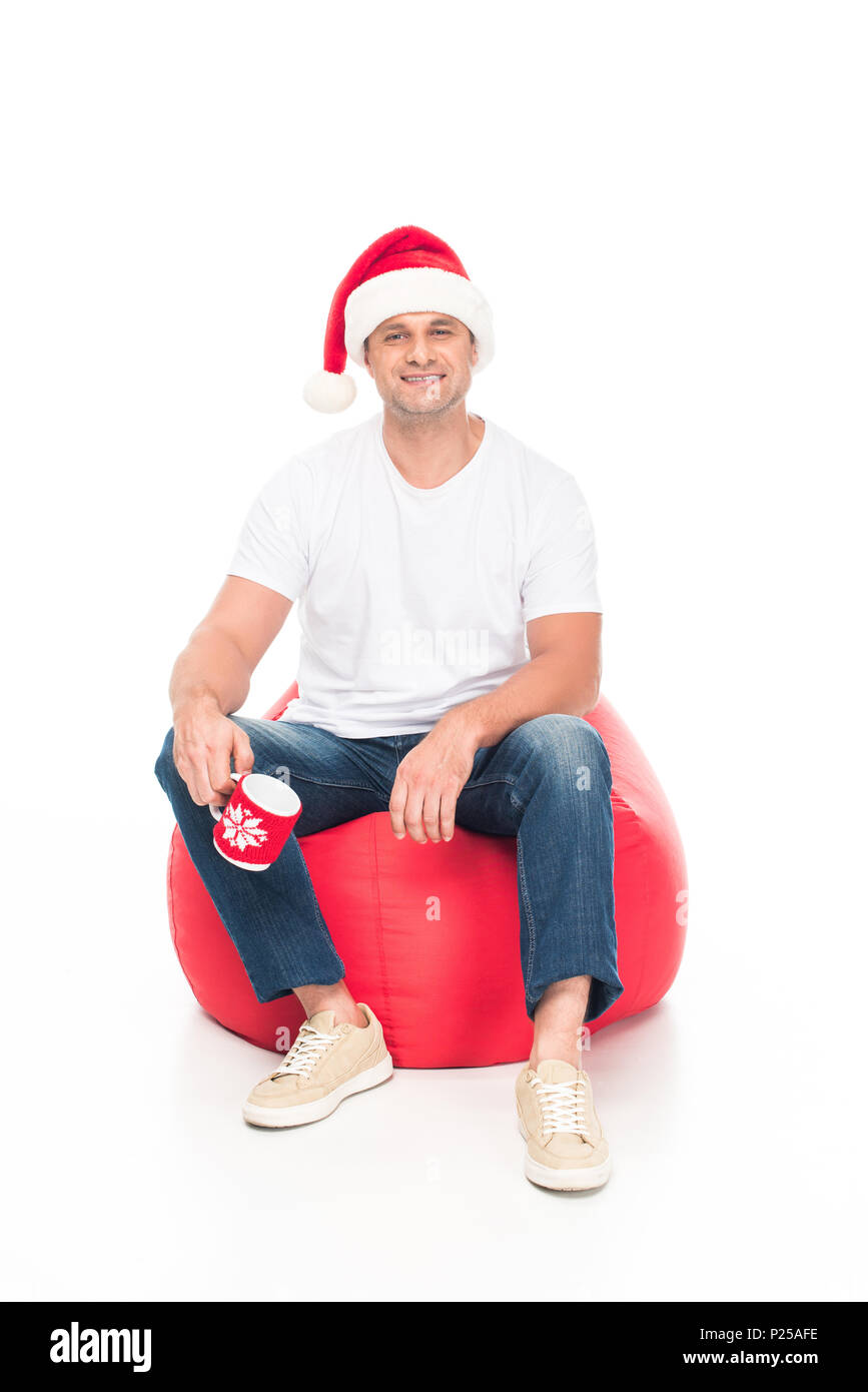 happy man in Santa hat with cup of coffee sitting in red bean bag chair, isolated on white - Stock Image