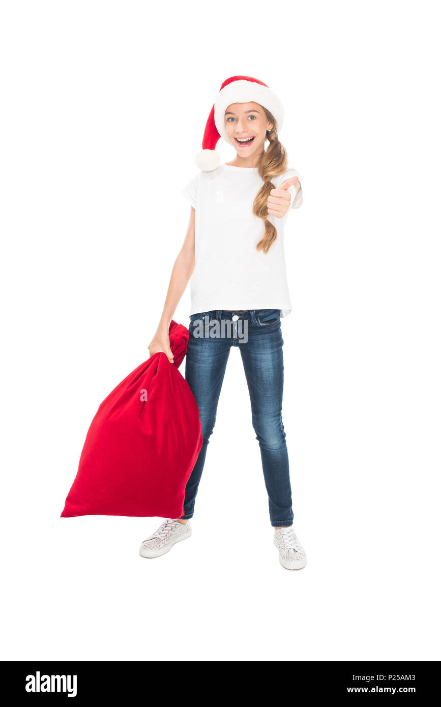 7de486629b029 Happy teenager in Santa hat with big bag full of presents for Christmas  showing thumb up