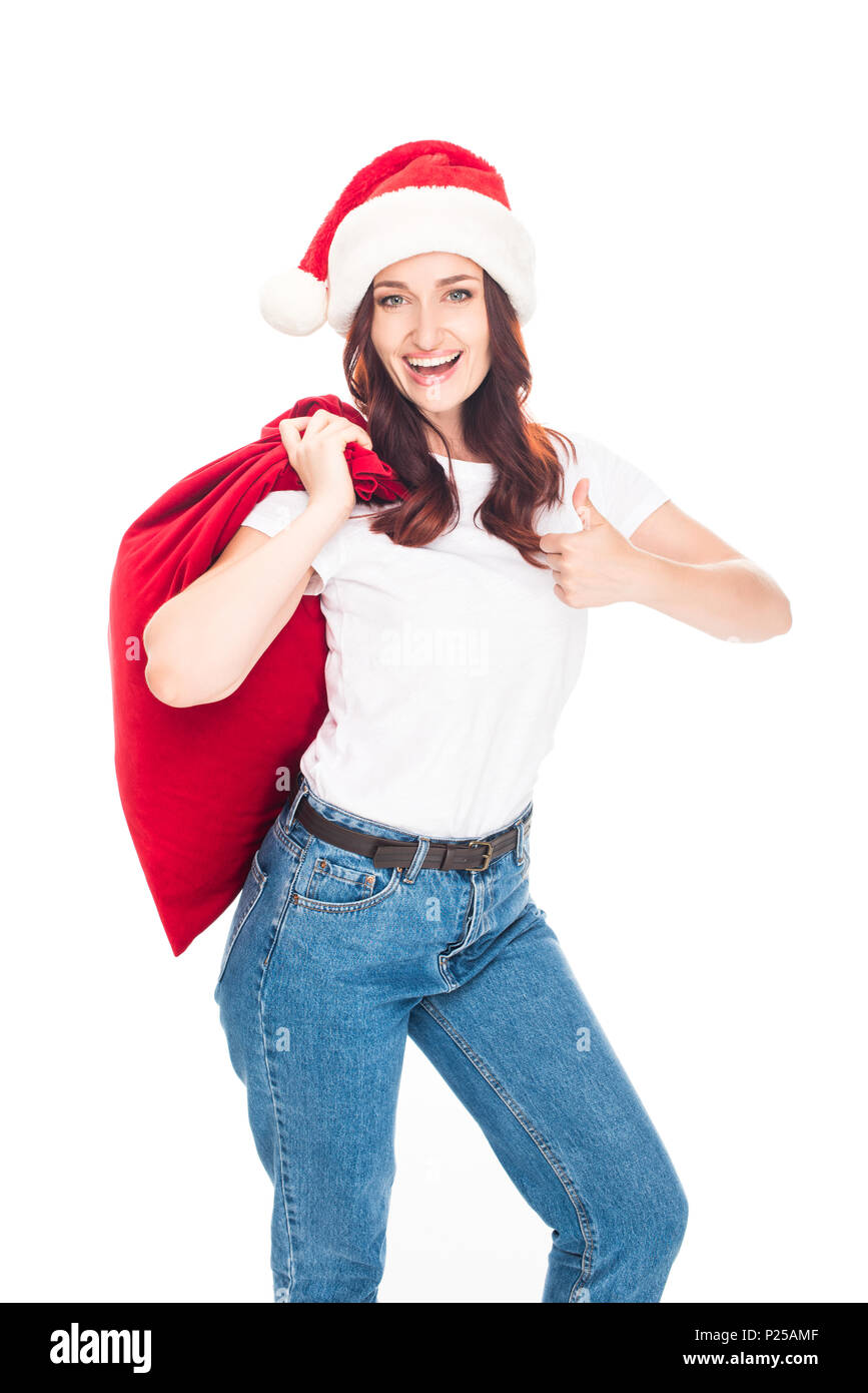 53231a96b8ef9 Happy girl in Santa hat with big bag full of presents for Christmas showing  thumb up